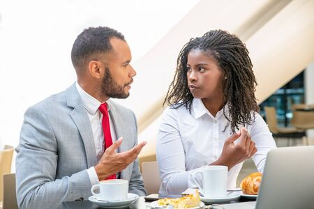 Excited diverse professionals discussing project during breakfast. Business man and woman sitting at laptop in cafe, drinking coffee, eating, talking. Lunch break concept Stock Photo - 129804694