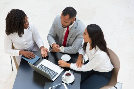 Diverse business team drinking coffee and discussing new ideas. Business man and women sitting at table with laptop and cups and talking. Corporate meeting concept. Stock Photo
