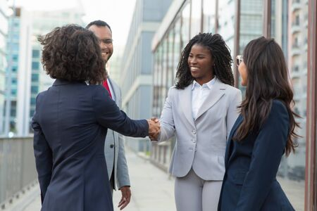 Satisfied business partners finishing up successful meeting. Business man and women standing near city building and shaking hands. Partnership concept