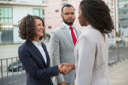 Consultant and customers meeting outside. Business man and women standing near city building and shaking hands. Diverse partners concept Stock Photo