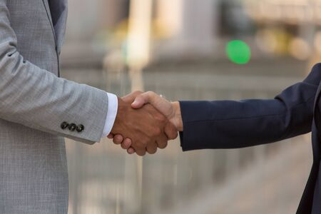 Business people shaking hands. Business man and woman meeting each other outside. Handshake concept