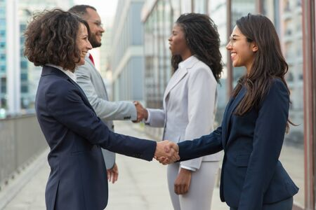 Positive business people finishing up successful meeting. Business man and women standing near city building and shaking hands. Closing deal concept Stock Photo