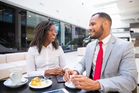 Diverse office friends enjoying coffee hour together. Business man and woman sitting in cafe, talking and laughing. Coffee break concept