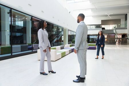 Three diverse colleagues meeting in office hall. Business man and women standing or walking in hallway, talking, smiling. Corporate relationship concept