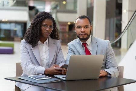 Serious business colleagues using laptop. Young African American business people sitting at table and using digital devices. Technology concept