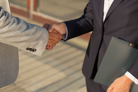 Business leader greeting colleague with folder. Business man and woman in office jackets shaking hands. Agreement concept