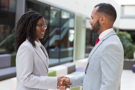 Happy successful business people greeting each other in office hallway. Business man and woman standing and shaking hands. Handshake concept