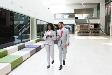 Diverse business professionals consulting internet on mobile phones. Business man and woman walking through office hallway and using smartphones. Wireless communication concept