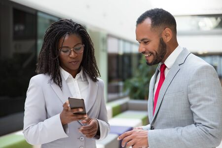 Cheerful coworkers watching content on mobile phone together. Business woman showing smartphone screen to male colleague. Digital communication concept Stock Photo