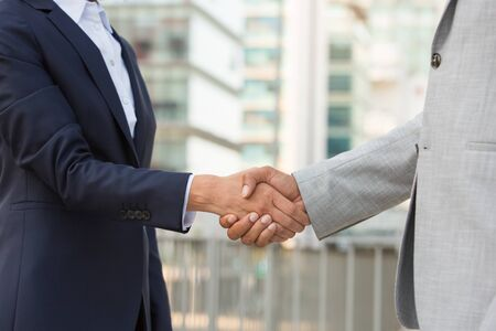 Partners greeting each other in business district. Business man and woman in office suits shaking hands outside. Handshake closeup concept