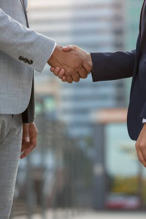 Businesspeople standing in city street and shaking hands. Business man and woman in office suits meeting outside. Successful partnership concept