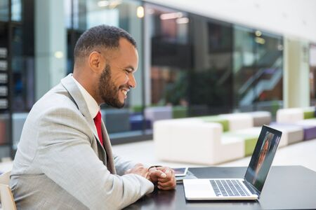 Smiling young businessman chatting via laptop. Cheerful African American businessman using laptop computer and having video chat with colleague at lunchtime. Communication concept