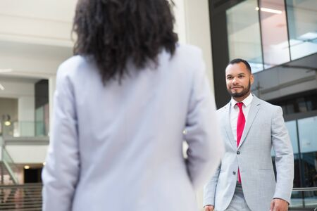 Happy friendly businessman going to meet his female colleague. Business man walking through hallway to woman in office suit. Partnership concept Stock Photo