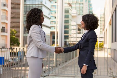 Happy businesswomen shaking hands outside. Caucasian and African American business ladies greeting each other on city building terrace. Communication concept Stock fotó