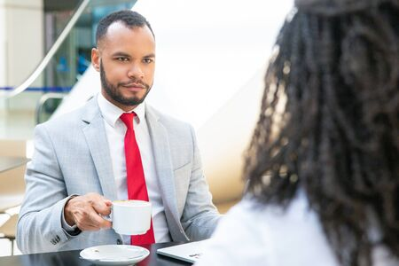Businessman discussing deal with partner over cup of coffee. Business man sitting at table opposite of his female colleague and drinking coffee. Corporate coffee break concept Stock fotó
