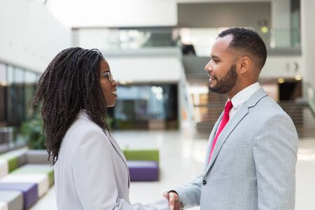 Happy confident business people finishing their meeting in office hallway. Business man and woman standing and shaking hands. Handshake concept