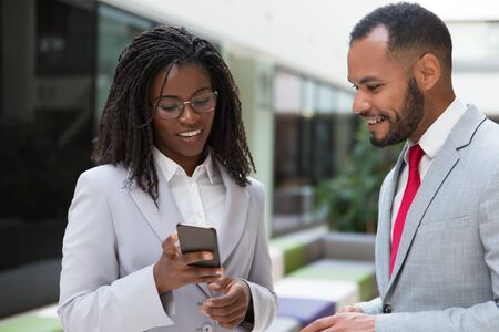 Excited happy colleagues looking at mobile phone screen together. Business woman showing smartphone content to male colleague. Wireless communication concept