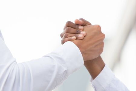Closeup of arm wrestling or friendly handshake gesture. Diverse business people shaking hands. Business communication concept