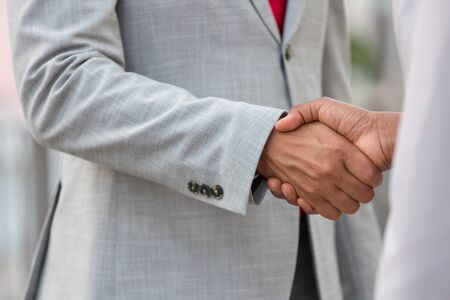 Business people in formal suits shaking hands. Business man greeting colleague. Handshake concept