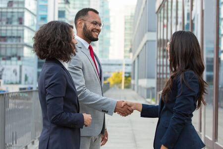 Side view of positive business people handshake. Business man and women standing in city street, shaking hands, smiling and talking. Welcoming concept