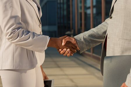 African American businesswoman shaking hands with male partner. Closeup of business colleagues handshake. Corporate meeting concept