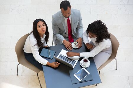 Business people discussing work issues over cup of coffee. Business man and women sitting at table with tablet, working on laptop, looking at camera. Business team concept