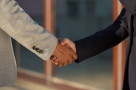 Businessman greeting female colleague. Business man and woman in office jackets shaking hands. Contract concept 写真素材