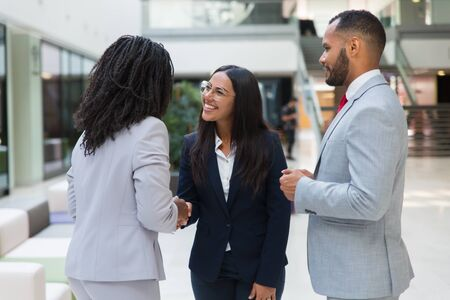 Female diverse business partners shaking hands with each other in hallway. Business man and women standing in office hall, talking and smiling. Successful partnership concept Stock Photo