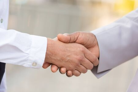 Closeup of business professionals handshake. Business man and woman shaking hands outside. Partnership concept