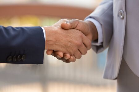 Closeup of business leaders handshake. Business people in office suits shaking hands with each other. Formal communication concept Stock Photo