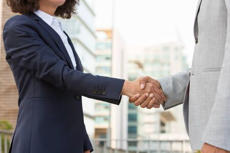 Partners meeting in business district. Business man and woman in office suits standing outside and shaking hands. Partnership concept