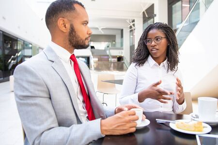 Diverse business colleagues chatting during coffee break. Business man and woman sitting in cafe, drinking coffee, talking and smiling. Coffee break concept Stock Photo