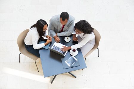 Business colleagues watching content on laptop while drinking coffee. Business man and women sitting at table with tablet, working on computer, looking at screen. Wireless communication concept