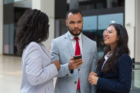 Multiethnic coworkers using smartphone. Confident young business colleagues standing together and using mobile phone. Communication concept