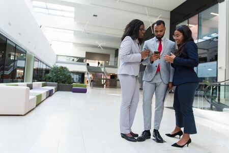 Multiethnic business colleagues using smartphone. Confident young business people standing together and using mobile phone, full length. Communication concept Stock Photo