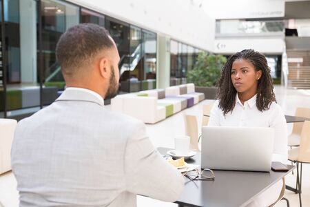 Giovani uomini d'affari che hanno pausa pranzo insieme. Uomo e donna di affari che si siedono alla tavola in caffè, usando il computer portatile e parlando. Pausa pranzo o concetto di riunione Archivio Fotografico