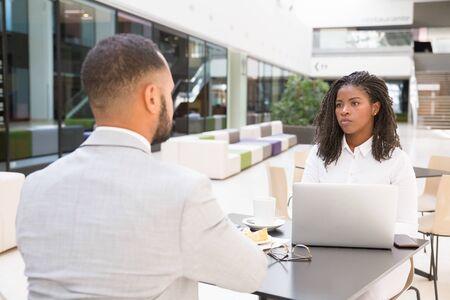 Junge Geschäftsleute, die zusammen Mittagspause machen. Geschäftsmann und Frau sitzen am Tisch im Café, mit Laptop und reden. Mittagspause oder Tagungskonzept Standard-Bild