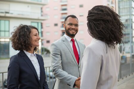 Agent meeting clients near office building. Business man and women standing in city, shaking hands and smiling. Friendly talk concept