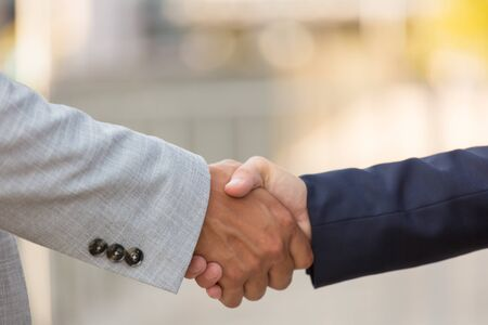 Closeup of business partners handshake. Business man and woman shaking hands with each other outside. Closing deal concept