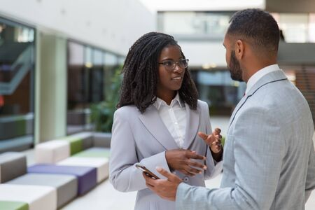 Smiling young business people talking. African American business colleagues standing together, using smartphone and talking. Communication concept Stock Photo