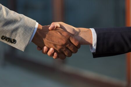 Business leaders meeting and greeting each other with handshake. Business man and woman in office jackets shaking hands. Successful deal concept Stock Photo