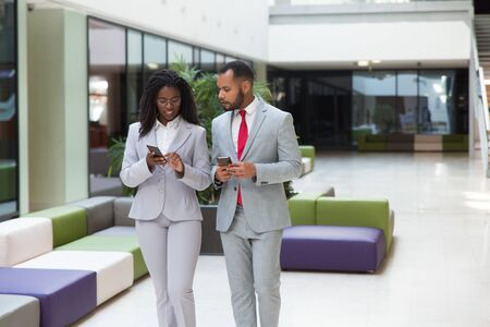 Diverse business professionals discussing content on mobile phones. Business woman showing smartphone screen to male colleague. Wireless communication concept