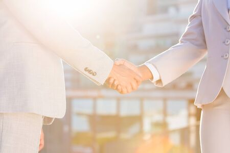 Business colleagues greeting each other in early morning. Business man and woman shaking hands in sunlight. City buildings in background. Agreement concept