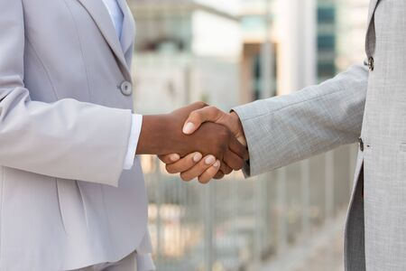 Diverse coworkers greeting each other outside. Multiethnic business man and woman in office suits shaking hands with each other. Business meeting concept