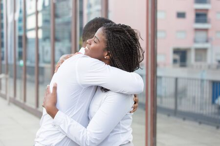 Diverse close friends hugging outside. Multiethnic couple standing in city street and embracing each other. Hug concept