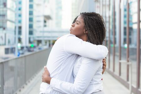 Diverse close friends wearing white shirts, hugging outside. Young couple standing in city street and embracing each other. Affection concept Stock Photo