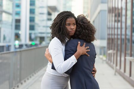 Diverse office friends greeting each other outside. Business women standing in city street and hugging. Bonding concept Stock Photo