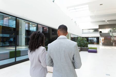 Young business colleagues discussing project on their way to office. Backs of business man and woman walking through hallway. Business team concept Stock Photo