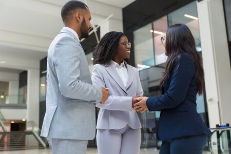 Friendly diverse businesswomen shaking hands with each other in hallway. Business man and women standing in office hall, smiling and discussing deal. Handshake concept