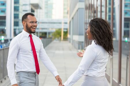 Surprised excited friends accidently meeting in city street. Happy business man and woman shouting for joy and ready to hug. Surprise or greeting concept